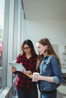 Geschäftsleute diskutieren über digitales tablet, während sie eine tasse kaffee trinken