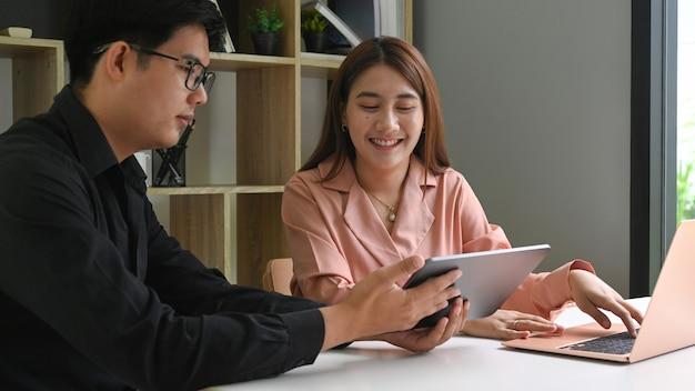 Geschäftsleute diskutieren und teilen informationen über digitale tablets im konferenzraum.