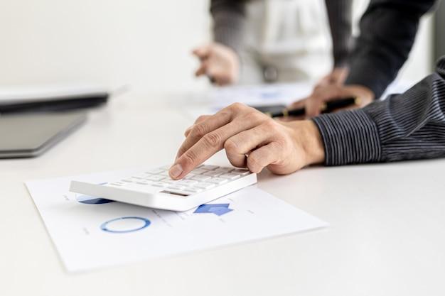 Geschäftsleute drücken den weißen taschenrechner, um die zahlen in den finanzunterlagen des unternehmens zu berechnen, die finanzabteilung bereitet das dokument vor und leitet es zur überprüfung vor dem treffen weiter.