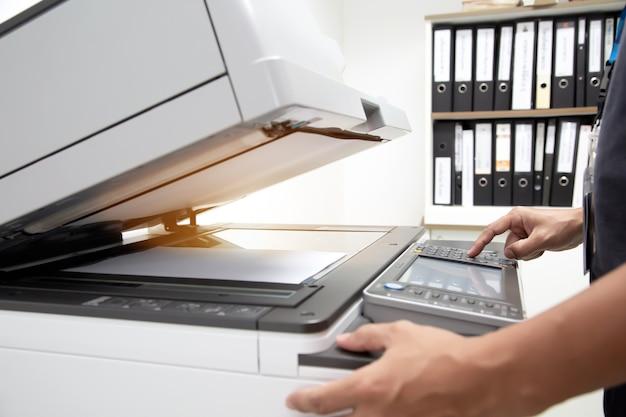 Geschäftsleute drücken die taste auf dem bedienfeld des fotokopierers