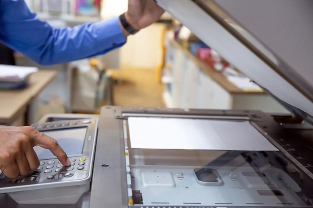 Geschäftsleute drücken die taste auf dem bedienfeld, um den fotokopierer zu verwenden.