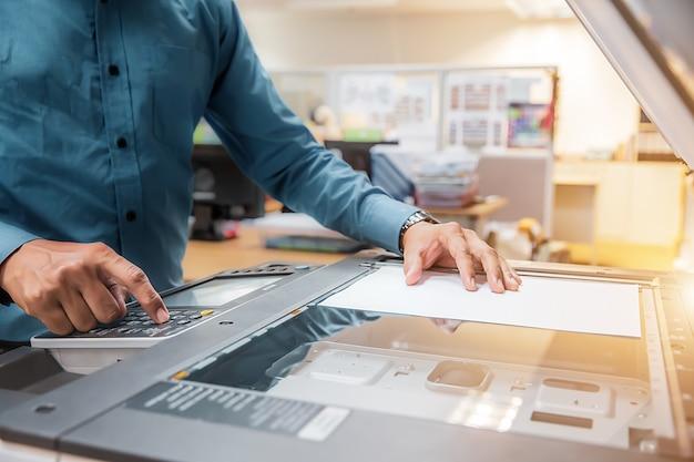 Geschäftsleute drücken die taste auf dem bedienfeld, um einen fotokopierer oder drucker zum ausdrucken und scannen von dokumentpapier im büro zu verwenden.
