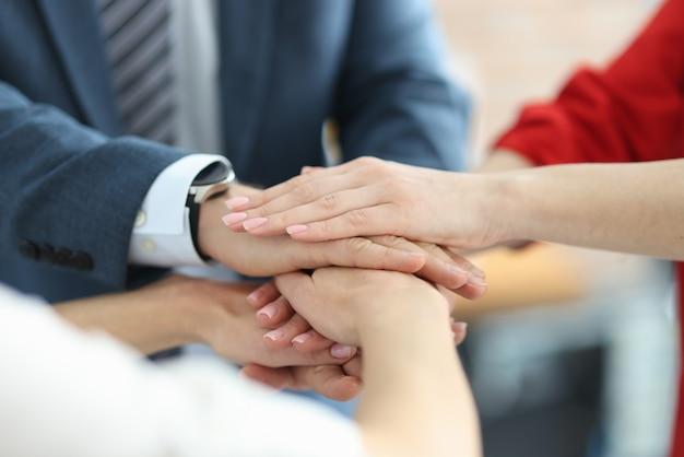 Geschäftsleute falten ihre hände zusammen in der büronahaufnahme