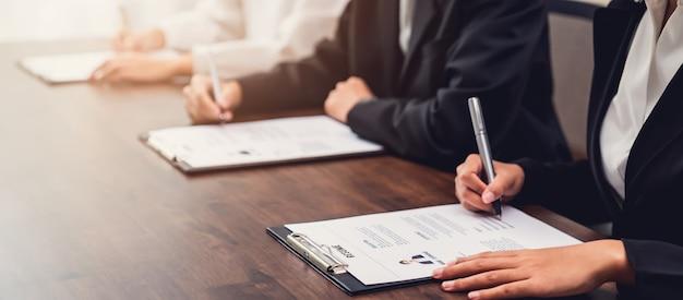 Geschäftsleute füllen die bewerbungsinformationen für den lebenslauf auf dem schreibtisch aus und bieten dem unternehmen die möglichkeit, der position des jobs zuzustimmen.