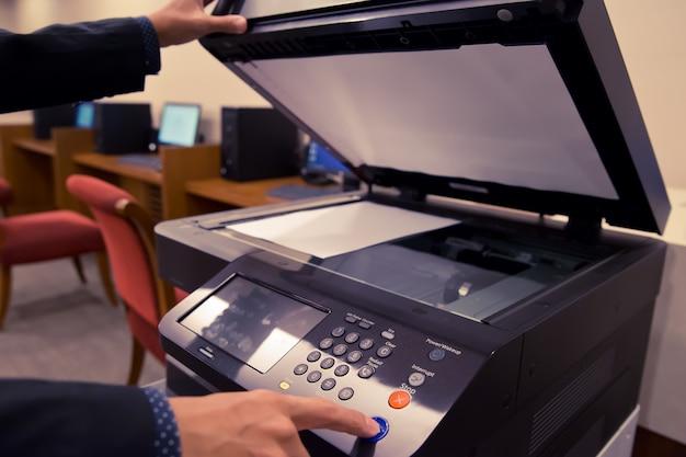 Geschäftsleute geben den knopf an der tafel des fotokoperators weiter.