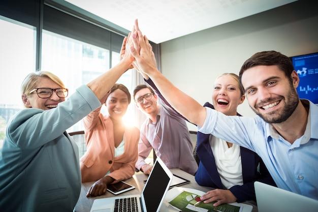 Geschäftsleute geben hohe fünf am schreibtisch