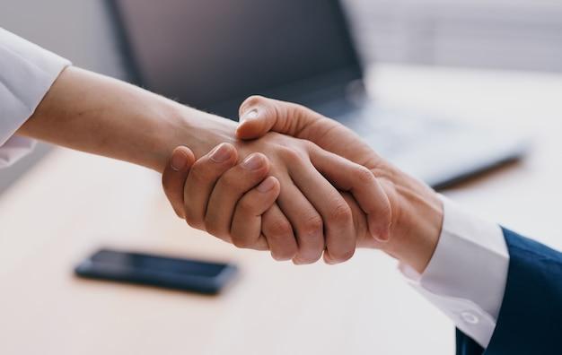 Geschäftsleute geben sich bei der arbeit die hand im büro verstehen sich die mitarbeiter gegenseitig