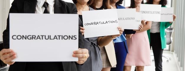 Geschäftsleute-gruppe in geschäftskleidung stellt reihe ein und hält papierfahne mit wortglückwünschen und zeigt der kamera. konzept der begrüßung und wertschätzung für den erfolg im job oder in der firma.
