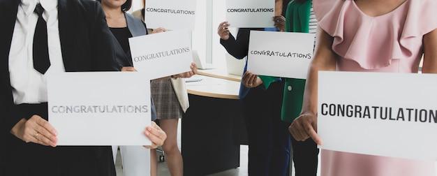 Geschäftsleute gruppieren sich in geschäftskleidung, die papierfahne mit wortglückwünschen hält und der kamera zeigt. konzept der begrüßung und wertschätzung für den erfolg im job oder in der firma.