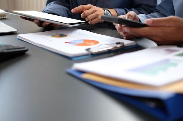 Geschäftsleute haben eine sitzung, der geschäftsmann, der mit team unter verwendung des intelligenten telefons der tablette arbeitet