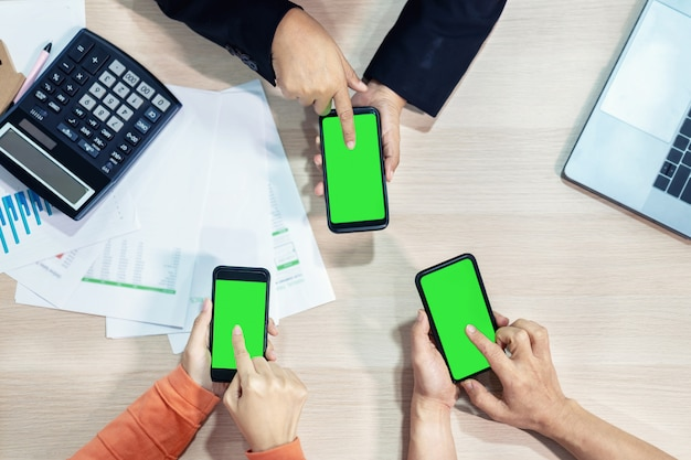 Geschäftsleute hände unter verwendung des grünen schirmes des intelligenten telefons auf draufsicht.