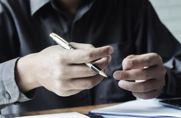 Geschäftsleute halten pennies und beschäftigen sich mit dem schreiben für meetings