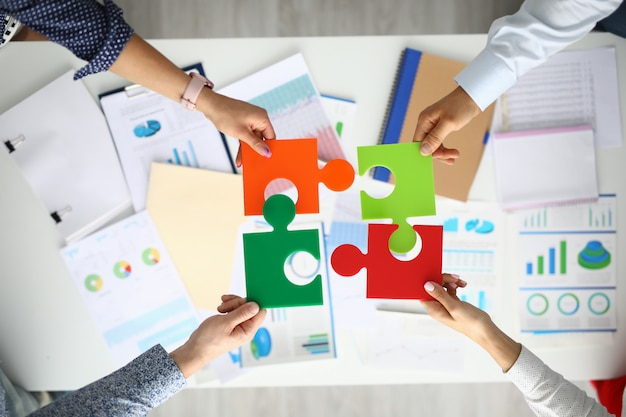 Geschäftsleute halten über der tabelle mehrfarbige rätsel mit kommerziellen indikatoren in der hand.