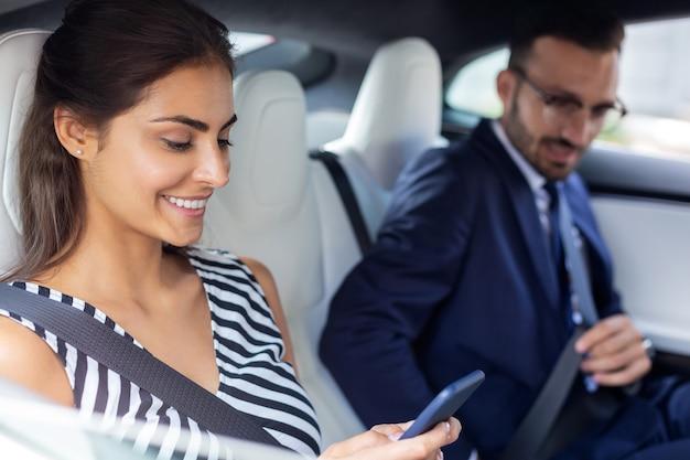 Geschäftsleute im auto. ein paar erfolgreiche wohlhabende geschäftsleute, die auf dem rücksitz im auto sitzen sitting