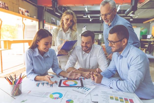 Geschäftsleute in den klassischen hemden benutzen eine digitale tablette
