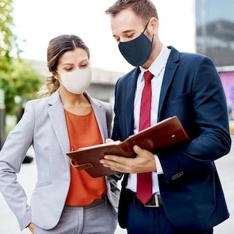 Geschäftsleute in der gesichtsmaske, die in der neuen normalität arbeitet