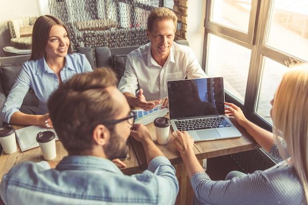 Geschäftsleute in der intelligenten freizeitkleidung besprechen angelegenheiten.