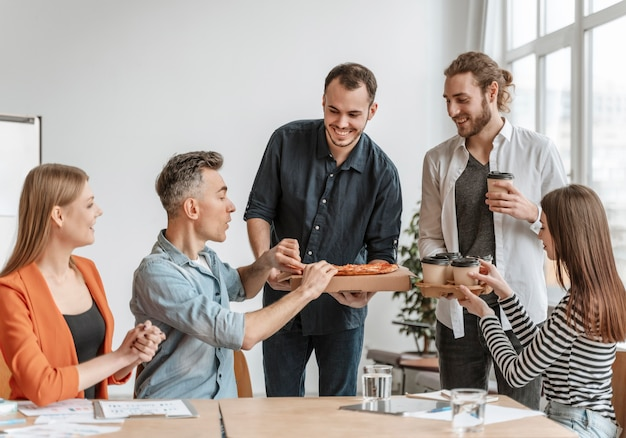 Geschäftsleute in der mittagspause essen pizza