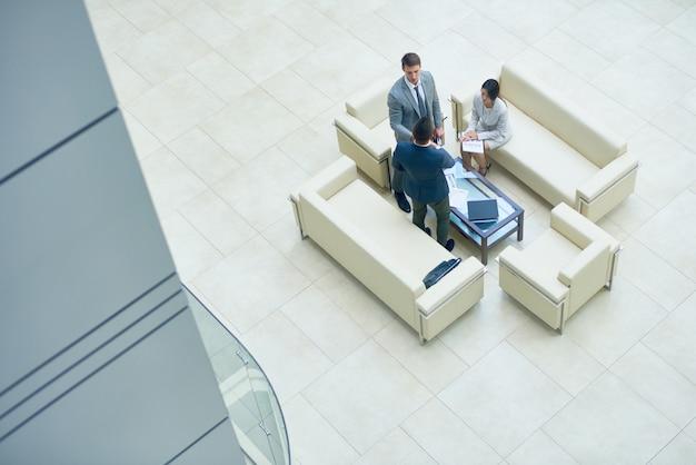 Geschäftsleute in einer besprechung auf weißen sofas