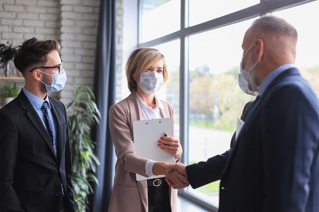 Geschäftsleute in medizinischen masken, die sich die hände schütteln und ein treffen beenden.