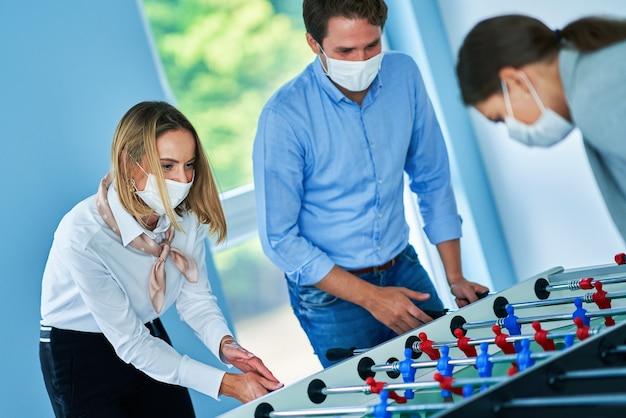 Geschäftsleute in schutzmasken, die tischtennis in gemeinsamen büroräumen spielen