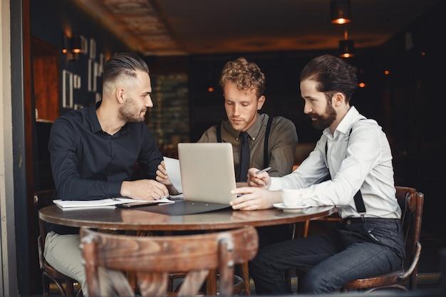Geschäftsleute in verhandlungen. bärtige männer sitzen am tisch. freunde reden.