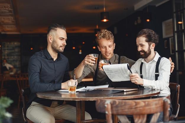 Geschäftsleute in verhandlungen. männer mit alkohol sitzen am tisch. freunde reden.