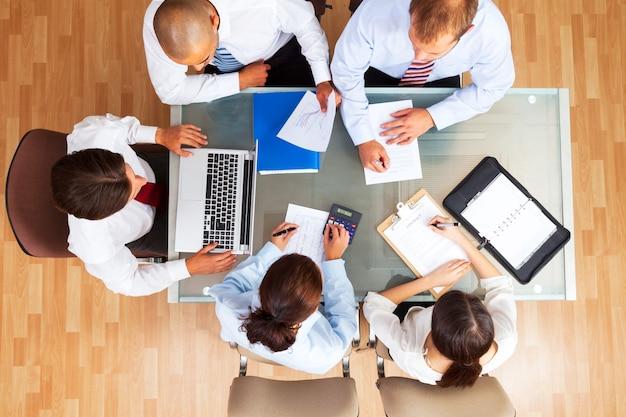 Geschäftsleute machen bericht am tisch mit diagrammen isoliert auf weiß