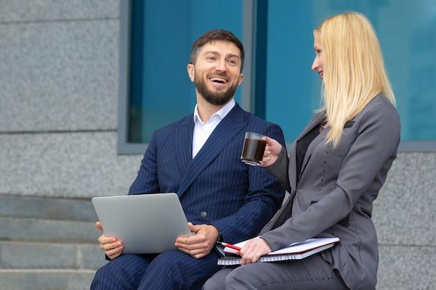 Geschäftsleute, mann und frau, die auf der treppe sitzen