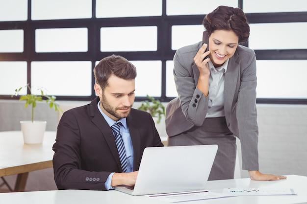 Geschäftsleute mit handy und laptop im büro