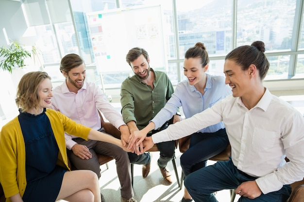 Geschäftsleute mit ihren händen gestapelt, während sie sitzen