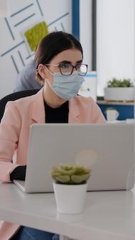 Geschäftsleute mit medizinischen gesichtsmasken, die während der coronavirus-pfanne in einem neuen normalen büro zusammenarbeiten...