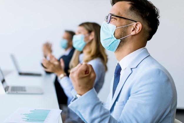 Geschäftsleute mit schutzmasken klatschen nach erfolgreichem geschäftstreffen im modernen büro in die hände