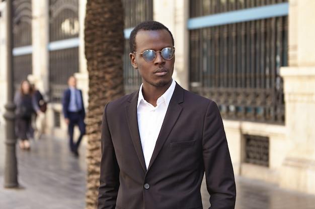 Geschäftsleute, mode und modernes urbanes lifestyle-konzept. gut gekleideter erfolgreicher bankier in stilvoller brille und anzug, der draußen steht und ernst aussieht, während er auf geschäftspartner zum mittagessen wartet
