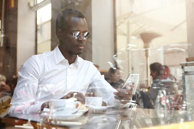 Geschäftsleute, moderner urbaner lebensstil und technologien. hübscher selbstbewusster afroamerikanischer geschäftsmann in den schattierungen und im weißen hemd, die sms schreiben oder e-mail auf handy während der kaffeepause im café abrufen
