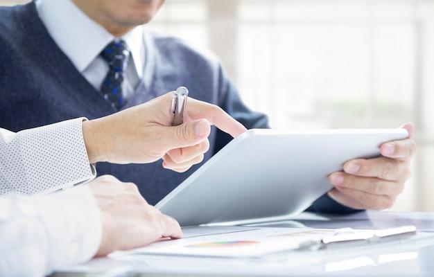 Geschäftsleute oder investoren, die den return on investment auf einem tablet-mobilgerät überprüfen.