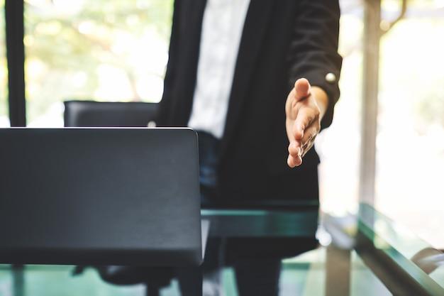 Geschäftsleute öffnen die hand, um jemandem im büro die hand zu geben