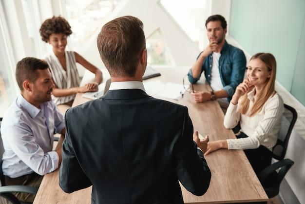 Geschäftsleute rückansicht eines geschäftsmannes in formeller kleidung, der etwas mit seinen kollegen bespricht