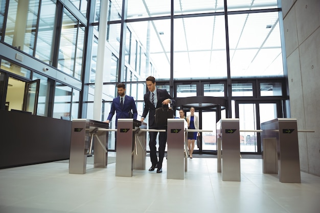 Geschäftsleute scannen ihre karten am drehkreuztor