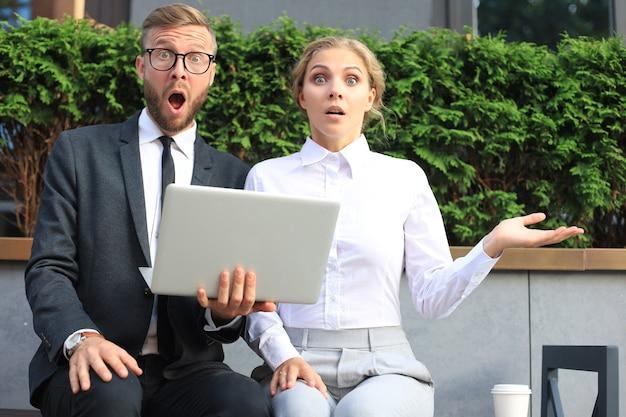 Geschäftsleute schockiert über informationen vom laptop.