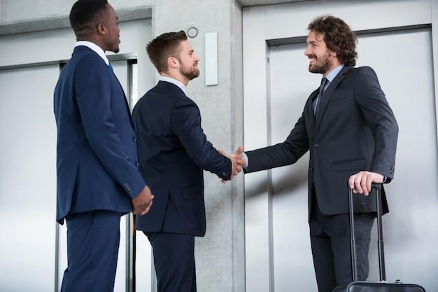 Geschäftsleute schütteln hände, während sie auf aufzug warten