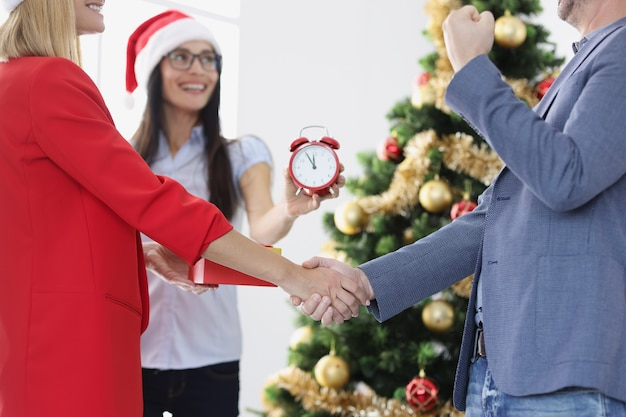 Geschäftsleute schütteln sich die hände vor dem hintergrund des neujahrsbaums, der verträge und zeit unterzeichnet