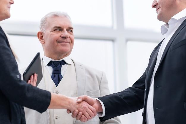 Geschäftsleute schütteln sich die hände, wenn sie sich im büro treffen. büro wochentags