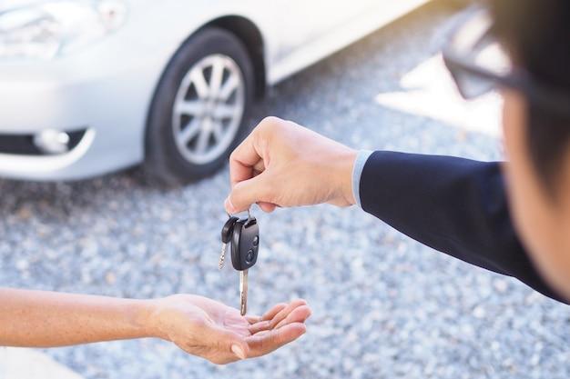 Geschäftsleute senden autoschlüssel an neue besitzer.