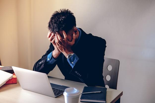 Geschäftsleute sind gestresst und hoffnungslos. er legte seine hände mit schmerzen auf das gesicht.
