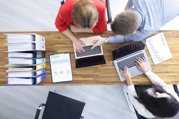 Geschäftsleute sitzen an ihrem schreibtisch und diskutieren über die entwicklungsstrategie