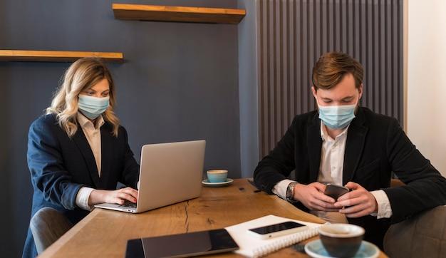 Geschäftsleute sprechen über ein neues projekt, während sie medizinische masken tragen