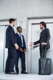 Geschäftsleute sprechen, während sie auf aufzug warten