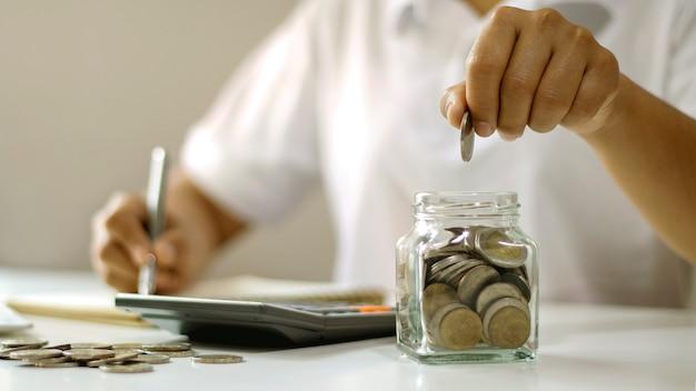 Geschäftsleute stecken münzen in glasflaschen sparkonto ideen und geld sparen.