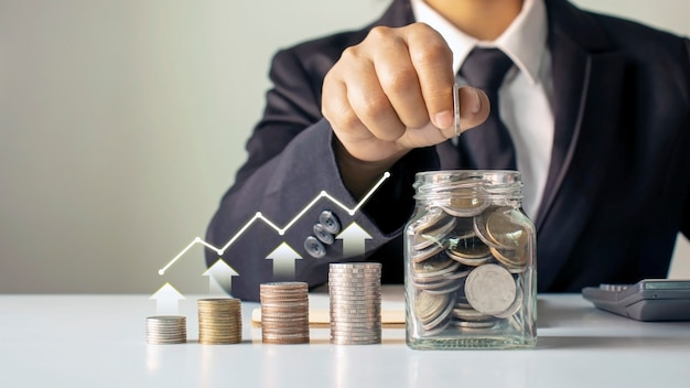Geschäftsleute stecken münzen in sparflaschen, darunter diagramme des finanzwachstums, geldsparende ideen und nachhaltige investitionen.